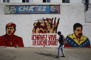 A woman walks past a mural depicting former Venezuelan President Hugo Chavez and incumbent President Nicolas Maduro.