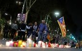 People walk with an Estelada (Catalan separatist flag) next to candles during a protest against the imprisonment of leaders of two of the largest Catalan separatist organizations who were jailed by Spain's High Court, in Barcelona, Spain, Oct. 17, 2017.