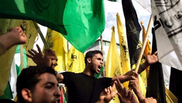 Palestinians wave Fatah and Hamas flags at the square of the Unknown Soldier in central Gaza City. (FILE)