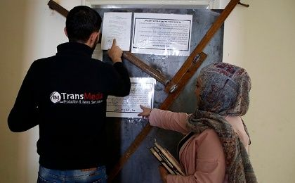 Employees of TransMedia look at a military order attached to their office doors in Hebron on October 18, 2017.