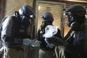 A U.N. chemical weapons expert, wearing a gas mask, holds a plastic bag containing samples from one of the sites of an alleged chemical weapons attack in the Ain Tarma neighbourhood of Damascus August 29, 2013.
