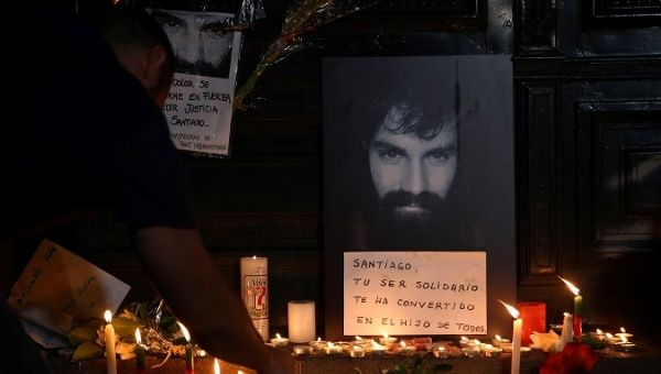 A man lights candles next to a portrait of Santiago Maldonado at the entrance of a judicial morgue in Buenos Aires, Argentina, October 20, 2017