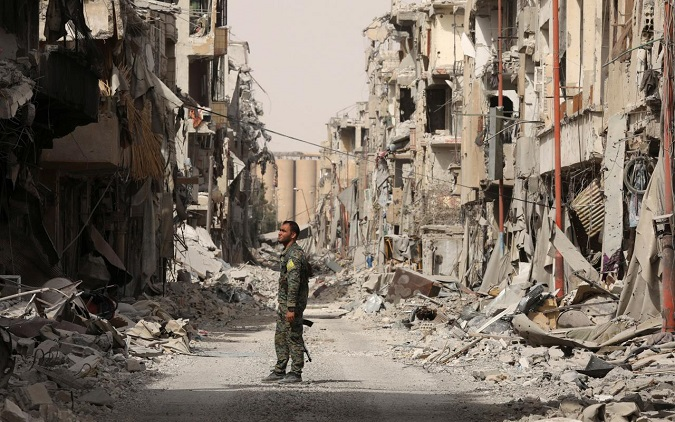A fighter from Syrian Democratic Forces (SDF) stands next to debris of damaged buildings in Raqqa, Syria September 25, 2017.