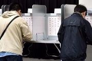 Japanese voters casting their ballots at the polls.