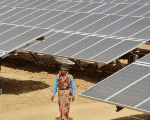 A worker walks through the installed solar modules at the Naini solar power plant in Allahabad