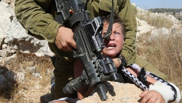 A 2015 photo shows an Israeli soldier attempting to arrest a Palestinian boy.