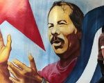 A man walks by a mural of Sandinista President Daniel Ortega.