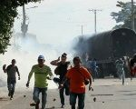 Colombian campesinos run after the ESMAD police threw tear gas.