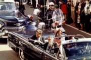 President John F. Kennedy and first lady Jacqueline Kennedy ride in the back seat of an open convertible moments before Kennedy was assassinated.