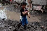 Boy walks in a muddied house in Nicaragua after heavy rains hit the country and neighboring Honduras.
