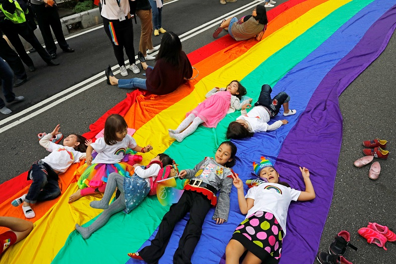 Children play on a giant rainbow flag as they take part in the parade.