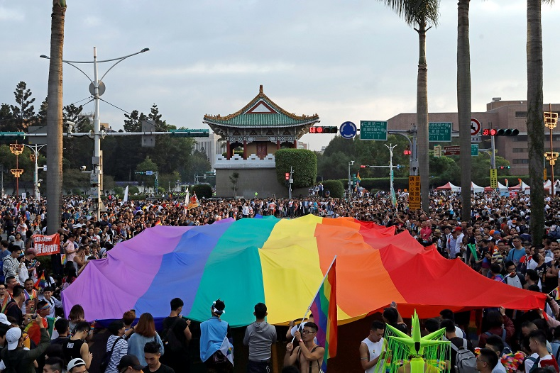Participants hold a giant rainbow flag at the rally.