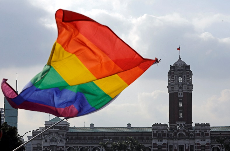 A participant waves a rainbow flag in front of the president