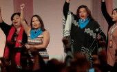 A group of Indigenous women raise their fists as they sing during the opening session of the three-day convention at Cobo Center in Detroit, Michigan.