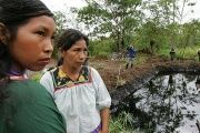 Cofan indigenous Women from Ecuador at the foot of the water body that shows the ecological destruction by the oil company..