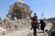 Displaced Iraqi civilians walk past the ruined Grand al-Nuri Mosque after fleeing from the Old City in Mosul.