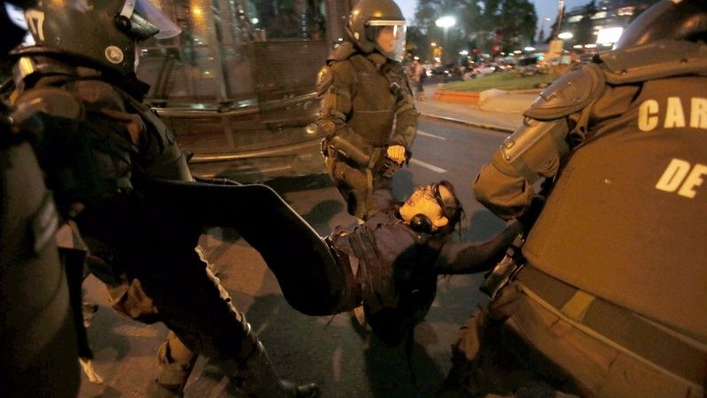 A member of a feminist organisations is detained by riot police during a rally against sexual harassment and gender violence in Santiago, Chile October 24, 2017.