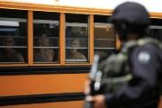 A Salvadoran policeman guards buses as 1,282 members of the Barrio 18 gang are transferred from a jail in Cojutepeque.