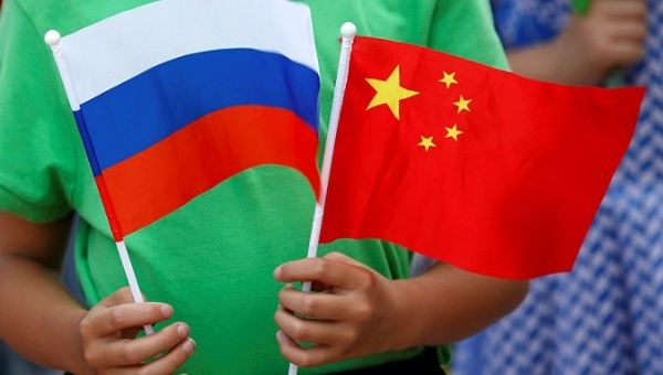 A child holds the national flags of Russia and China prior to a welcoming ceremony.
