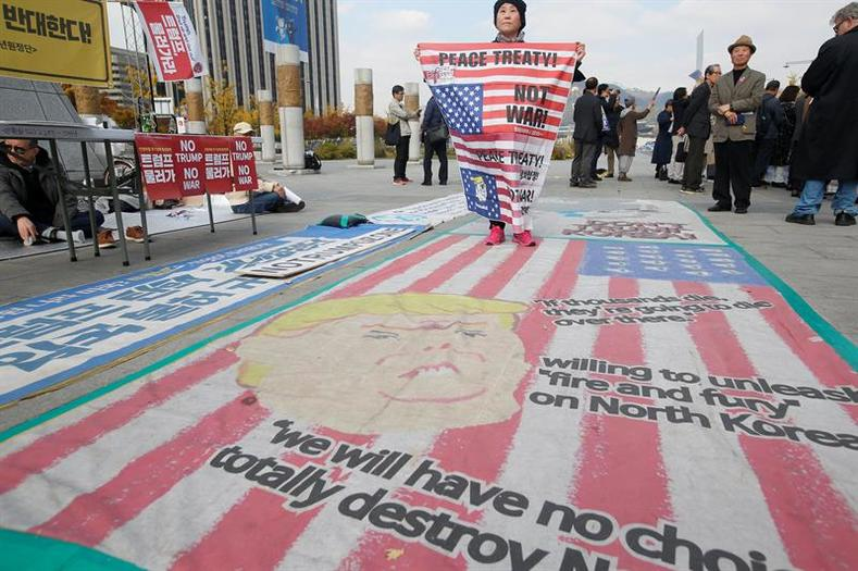 A South Korean protester stands on a cartoon depiction of US President Donald J. Trump during a rally held to show opposition to the US President