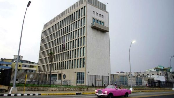 A car with tourists drives past the U.S. Embassy in Havana, Cuba.