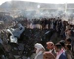 People gather at the site of an air strike in the northwestern city of Saada, Yemen.