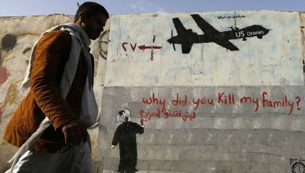 A man walks past a graffiti denouncing strikes by U.S. drones in Yemen.