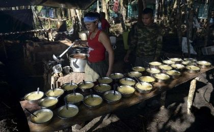 A member of the FARC serves soup for lunch at their camp in El Diamante, Colombia, last year.
