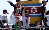 Children from the DPRK wave during a tour on the Yalu River in Sinuiju, near the Chinese border city of Dandong.