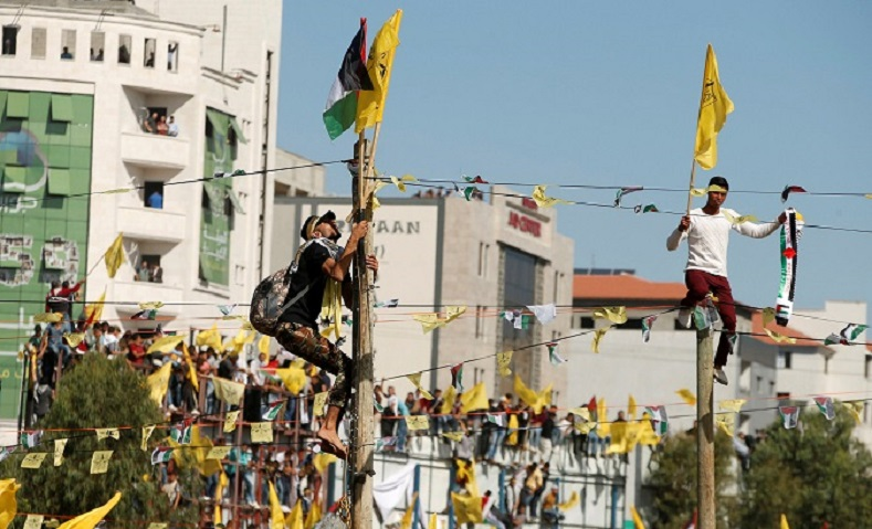 Fatah members honor Arafat waving flags and listening to speech by current Fatah leaders.