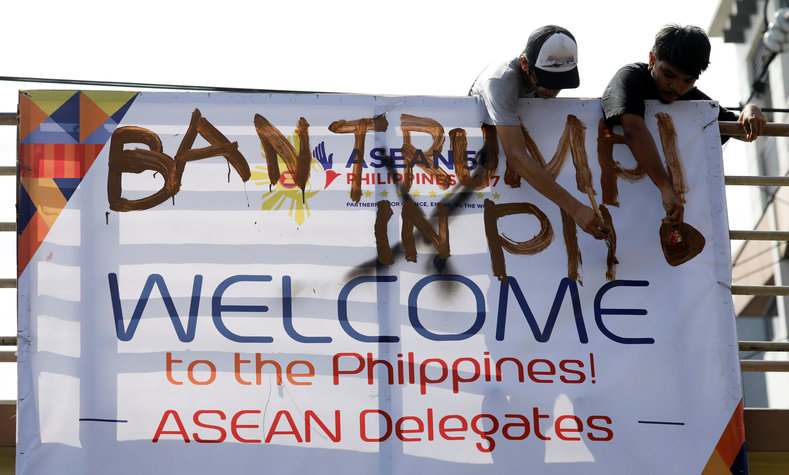 Anti-Trump protesters deface an ASEAN poster as they oppose the planned visit of U.S. President Donald Trump who is attending the ASEAN leaders summit in Manila, Philippines November 7, 2017.