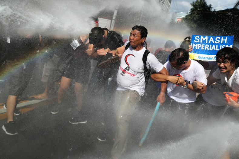 Protesters are hit by a water cannon as they try to march towards the U.S. embassy during a rally against U.S. President Donald Trump