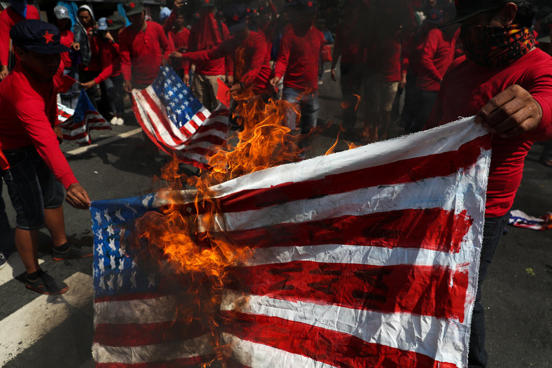 Protesters burn homemade U.S. flags to denounce the visit of U.S. President Donald Trump, who will attend the 31st Association of Southeast Asian Nations (ASEAN) leaders summit, during a protest along a main street in metro Manila, Philippines, November 12, 2017.