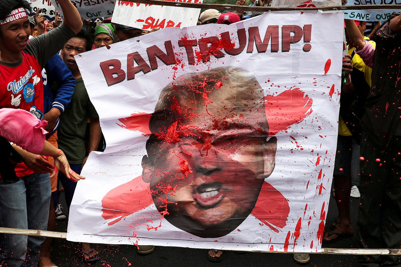 Protesters throw red paint to a picture of U.S. President Donald Trump during a rally against his visit in Manila, Philippines, November 11, 2017.