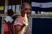A woman shows her ink-stained thumb after voting in the municipal elections at a polling station in Managua, Nicaragua November 5, 2017.