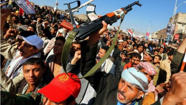 Yemenis carry signs and weapons protesting the Saudi-led war and air, land and sea blockade against the country.