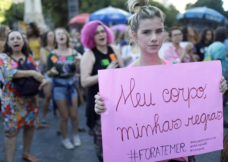 "Protesters demonstrate with a sign that reads ""My body, my rules"" and ""Out Temer""  in Rio de Janeiro."