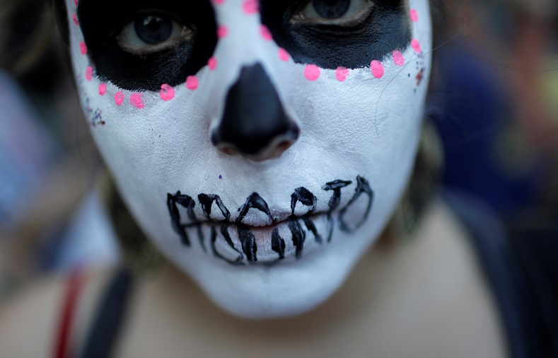 A woman demonstrates with a face painting representing a dead woman after an illegal abortion, in Rio de Janeiro.