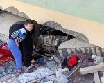 A man and child look at a damaged building following the 7.3 magnitude earthquake in the town of Darbandikhan, Iraq.