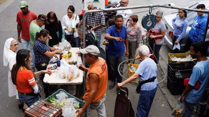 People queue to pay for their fruits and vegetables at a street market in Caracas, Venezuela November 13, 2017.