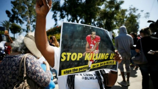 "A protester demonstrates and holds a sign with Colin Kaepernick on it in support of NFL players who ""take a knee"" at an NFL football game in Carson, California, U.S. Oct. 1, 2017."
