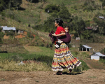 A Guatemalan Indigenous woman carries a child on her back in the village of Pumbach, 130 miles from Guatemala city