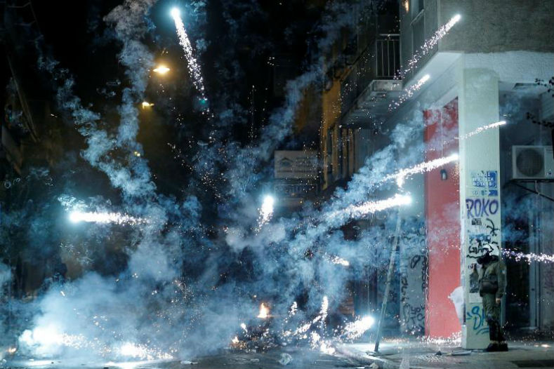 A firework explodes next to a riot policeman in Athens, Greece during clashes following a rally marking the 44th anniversary of a 1973 student uprising against the Greek military dictatorship.