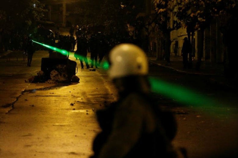 Protesters point a laser at riot police during clashes following a rally marking the 44th anniversary of a 1973 student uprising against the military dictatorship.