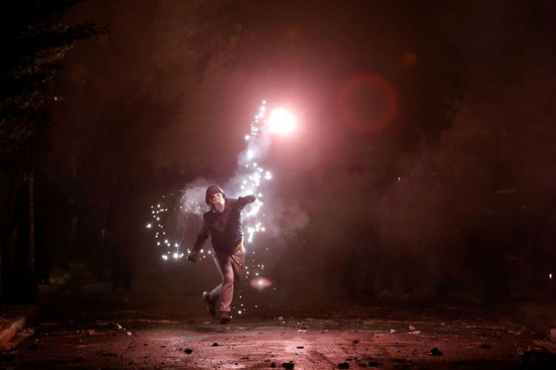 A hooded protester throws a flare during clashes.