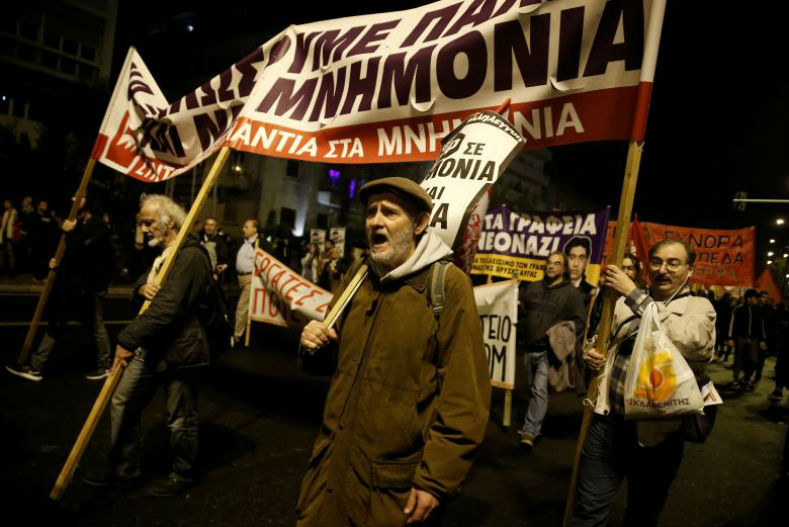 Protesters shout slogans whil marching in the streets of Athens.