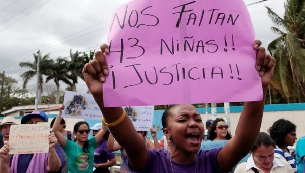 "An activist holds a sign that reads ""We are missing 43 girls! Justice!"" during a protest outside Guatemala"