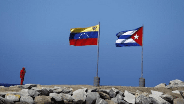 A worker stands next to Venezuelan and Cuban flags in a beach in La Guaira, in the state of Vargas outside Caracas.