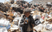 A boy drinks expired juice on a pile of rubbish at a landfill site on the outskirts of Sanaa, Yemen, November 2016.