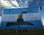 People walk behind an Argentine national flag displayed on a fence in Mar del Plata, Argentina, Nov. 22, 2017. The words on the flag read: